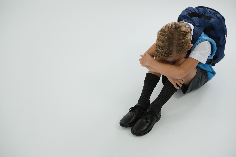 Sad schoolboy sitting on white background